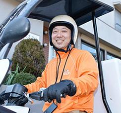 バイクにのった笑顔のスタッフ